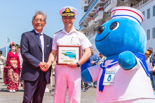 望月会長とゴールデン・プリンセスの船長、清水区のマスコット「シズラ」。Chairman Mochizuki with the captain of the Golden Princess and Shimizu Ward Mascot Shizulla (April 26, 2018)